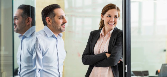 man and woman smiling in office setting