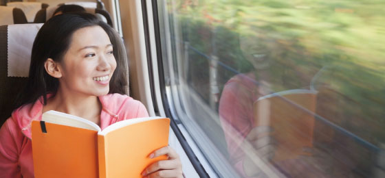 asian woman with book on a train